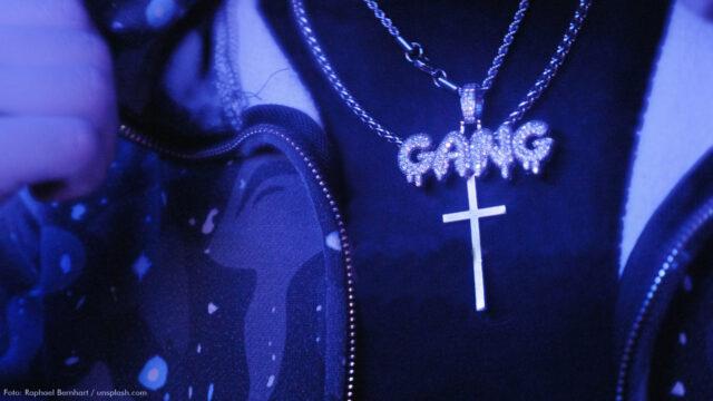 """Unter einer geöffneten Jacke trägt ein Mensch eine mit Strass-Steinen besetzte Kette mit dem Wort """"GANG"""". Darunter ist eine weitere Kette mit einem Kreuz."""