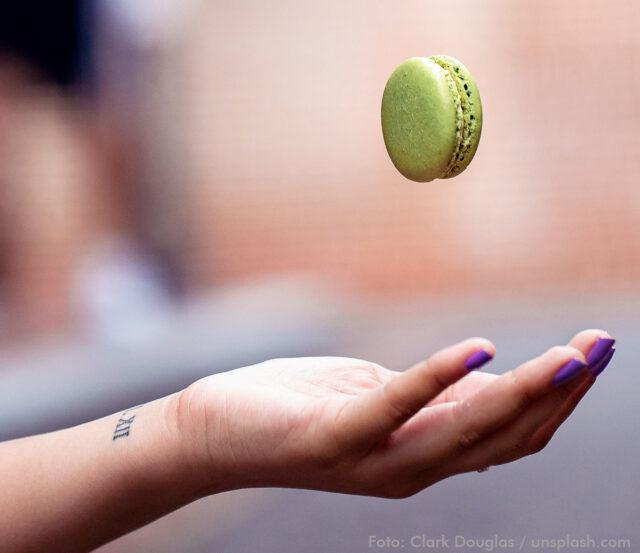 Ein Macaron schwebt in der Luft. Darunter ist eine offene Hand, um es aufzufangen.