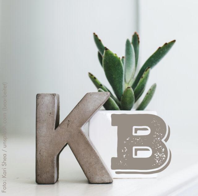 """Auf einer glatten hellen Oberfläche steht ein """"K"""" aus Beton, daneben ist ein """"B"""" abgebildet und dahinter steht eine Topfpflanze."""