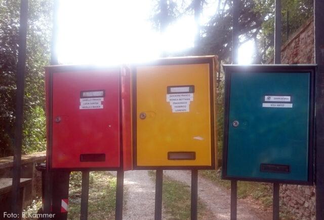 An einem Metallzaun hängen drei Briefkästen mit mehreren italienischen Namen. Der erste ist rot, der zweite gelb, der dritte blau. Im Hintergrund ist ein Weg, Bäume und eine Mauer.