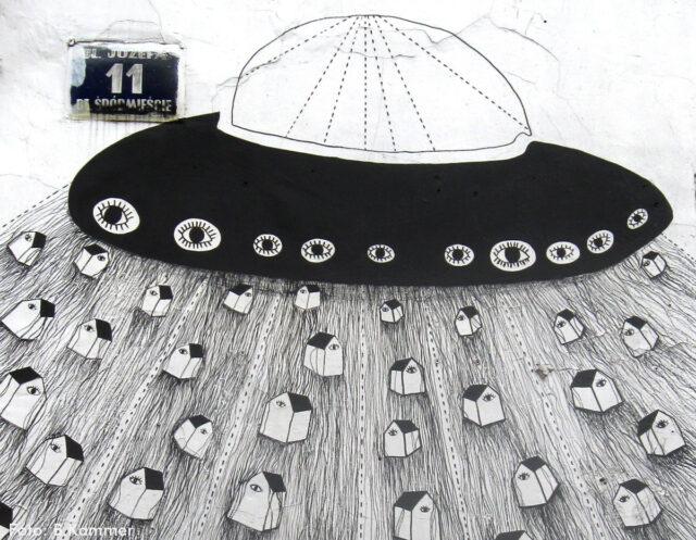 Ein schwarz-weißes Graffiti zeigt ein UFO, an dessen unterem Rand viele Augen abgebildet sind. Es führen viele Strahlen zur Unterseite des UFOs. Darauf sind viele kleine Häuser abgebildet.