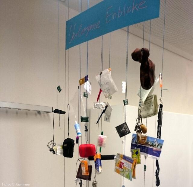 """Ein Mobile mit dem Inhalt eines Rucksacks, z.B. Schreibutensilien, Karten, Pflegeprodukten u.a. hängt von der Decke. Darüber hängt ein Schild """"Verborgene Einblicke""""."""