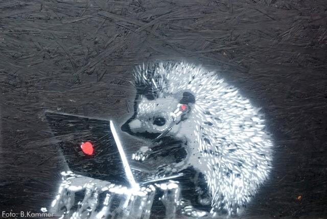 Ein Stencil silber auf schwarz: Ein Igel tippt an einem Laptop, auf dessen Rückseite ein roter Punkt ist. Der Igel trägt ein Headset. Der Laptop steht auf einem Baumstumpf.