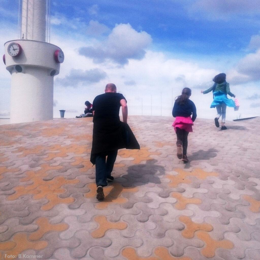 Ein Mann und zwei Mädchen rennen einen gepflasterten Hügel hinauf. Links im Hintergrund ist der untere Teil einer Säule zu sehen. Daran hängen Uhren. (Es ist 14.55 Uhr.) Oben auf dem Hügel sitzt eine Person im Schneidersitz. Im Hintergrund ist ein blauer Himmel mit Wolken.