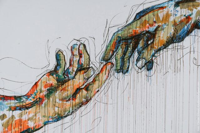Ein Graffiti: Zwei Hände berühren sich fast. Die eine wird von unten links ausgestreckt, die andere von oben reichts. Das Motiv geht auf Michelangelos Fresko in der Sixtinischen Kapelle zurück.