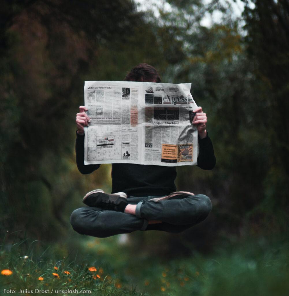 Ein Mensch im Pullover, Jeans und Turnschuhen sitzt im Schneidersitz. Dabei schwebt er über einer Blumenwiese. In den Händen hält er eine aufgeschlagene Zeitung (express). Dahinter verbirgt sich sein Gesicht und Oberkörper. Der Hintergrund ist verschwommen. Man kann erahnen, dass es Bäume und Sträucher sind.